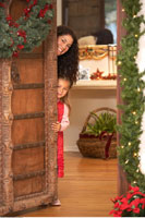 Mother and Daughter Peeking Around Door at Christmas