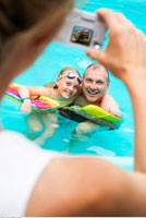 Woman Taking Picture of Father And Daughter in Swimming Pool