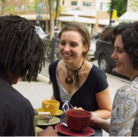 Three Young People Having Coffee At A Sidewalk Cafe