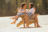Young Couple Cuddling In An Adirondack Chair On The Beach