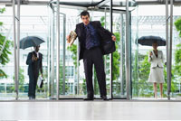 Business People Arriving at Office Building in Rain