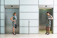 Two Businesswomen at Elevators Wearing Same Dress