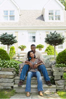 Man and Woman Sitting on Steps In Front of House
