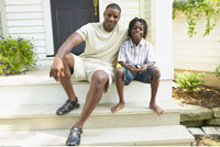 Father and Son Sitting On Steps Of House