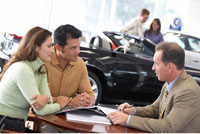 Couple Speaking with Car Salesman