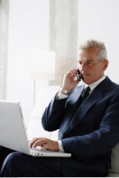 Businessman on Cellular Phone Using Laptop