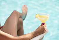 Woman Sitting at Pool Side with Drink