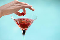 Hand Removing Raspberry from Martini