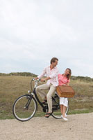 Couple Riding Bicycle and Carrying Picnic Basket