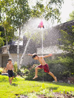 Boys Playing With Sprinkler