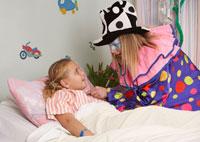 Clown Examining Child in HospitalBed