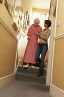 Woman Helping Senior WomanDescend Stairs