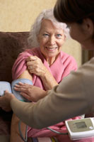 Woman Checking Senior Woman'sBlood Pressure