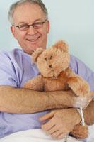 Man in Hospital Bed, HoldingTeddy Bear
