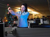 Businesswoman DecoratingChristmas Tree