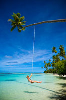 Woman Swinging from Palm Tree