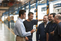 Man and Workers in Automotive Plant
