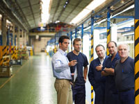 Man Talking to Workers inCar Factory