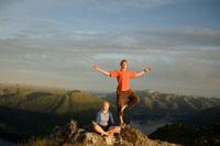 Couple Doing Yoga on MountainSummit