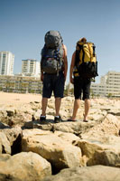 Backpackers Looking at City fromBeach