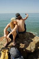 Backpackers on Rocks by Ocean