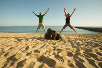 Backpackers Jumping on Beach