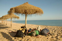 Backpackers Resting on Beach