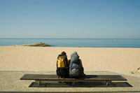 Backpackers on Bench by Ocean