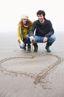 Couple Drawing Heart in Sand