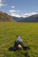 Man Lying ing Grass by Mountains