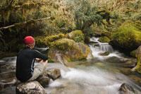 Man Watching Rapids in Creek