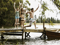 Friends jumping off dock