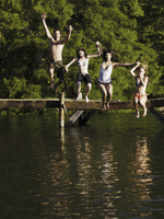 Multi-ethnic friends jumping off dock