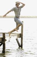 Man in clothing jumping off dock 20025266959| 写真素材・ストックフォト・画像・イラスト素材|アマナイメージズ