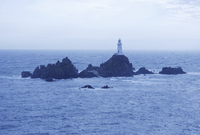 The Corbiere Lighthouse during high tide, at dusk, in the south west of Jersey, Channel Islands, UK