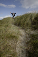 Businessman with arms wide open outdoors, Sylt, North Frisian Islands, Germany