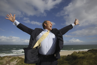 Happy businessman with arms wide open at beach, Sylt, North Frisian Islands, Germany