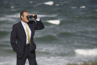 Businessman looking through binoculars at beach, Sylt, North Frisian Islands, Germany