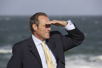 Businessman standing at beach and looking into distance, Sylt, North Frisian Islands, Germany