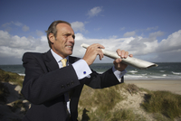 Businessman holding newspaper as a telescope at beach, Sylt, North Frisian Islands, Germany