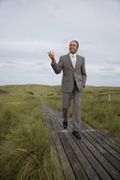 Mature businessman walking on walkway at beach, Sylt, North Frisian Islands, Germany