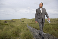 Mature businessman walking on walkway holding newspaper, Sylt, North Frisian Islands, Germany 20025271210| 写真素材・ストックフォト・画像・イラスト素材|アマナイメージズ