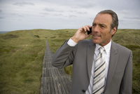 Mature businessman on the phone outdoors, Sylt, North Frisian Islands, Germany