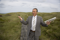 Mature businessman holding a newspaper outdoors, Sylt, North Frisian Islands, Germany