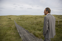 Mature businessman walking on walkway, Sylt, North Frisian Islands, Germany