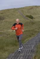 Senior man jogging on walkway, Sylt, North Frisian Islands, Germany 20025271216| 写真素材・ストックフォト・画像・イラスト素材|アマナイメージズ