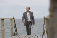 Mature businessman walking up steps at beach, Sylt, North Frisian Islands, Germany
