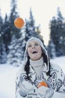 Woman juggling oranges in snow