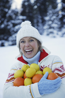 Woman holding oranges and lemons in snow