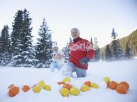 Couple walking toward oranges and lemons in snow